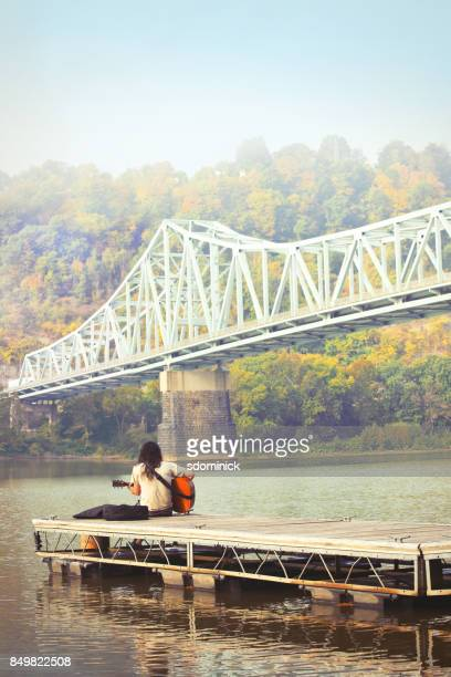Man Playing Guitar On Boat Dock on Beautiful Fall Morning