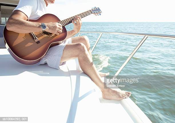 Man playing guitar on deck of yacht, low section