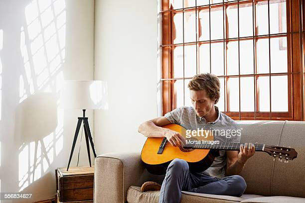 Man playing guitar on sofa at home