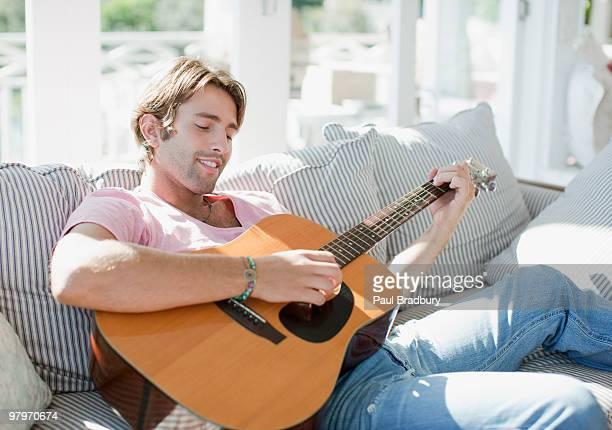 Man playing guitar on sofa