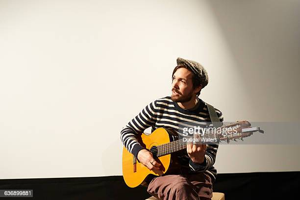 man playing guitar on stage. - musician stock pictures, royalty-free photos & images