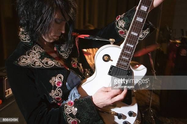 man playing guitar - glam rock stock pictures, royalty-free photos & images