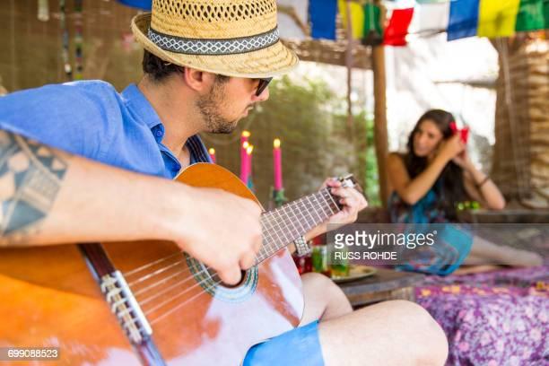 Man playing guitar serenading woman