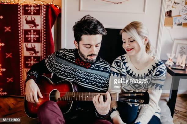Hombre tocando la guitarra a su girlfreind, Navidad
