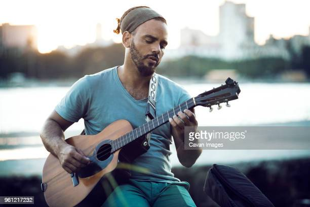 man playing guitar while sitting at lakeshore during sunset - only mid adult men stock pictures, royalty-free photos & images