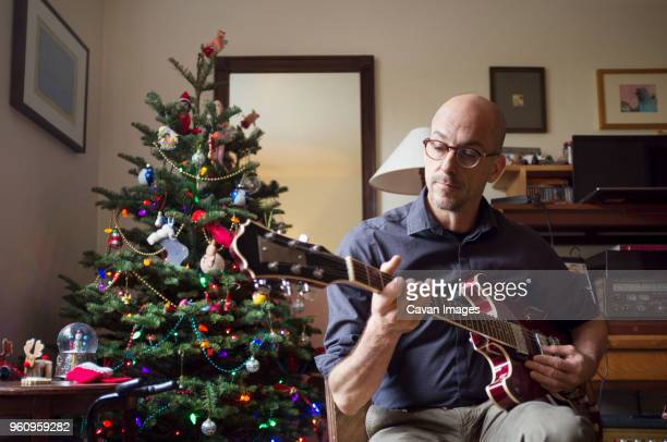 Man playing guitar while sitting by Christmas tree at home