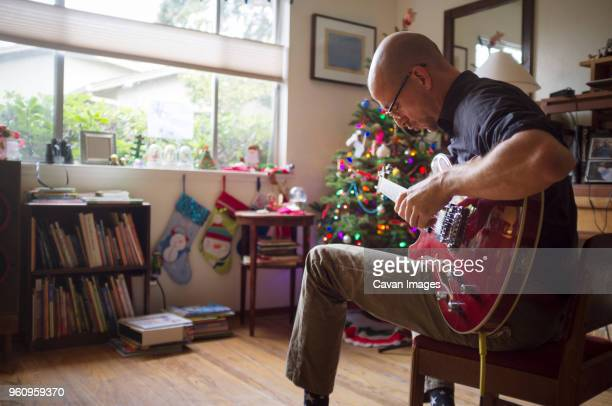 Man playing guitar while sitting on chair at home during Christmas