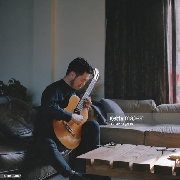 man playing guitar while sitting on sofa at home - guitarist stock pictures, royalty-free photos & images