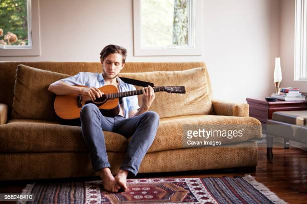 man playing guitar while sitting on sofa - gitarre stock-fotos und bilder