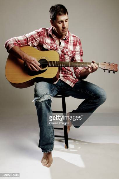 man playing guitar while sitting on stool against white background - plucking an instrument stock pictures, royalty-free photos & images