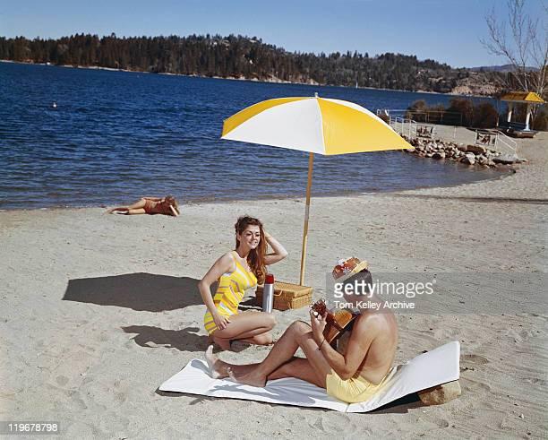 Homme jouant de la guitare et femme dansant sur la plage