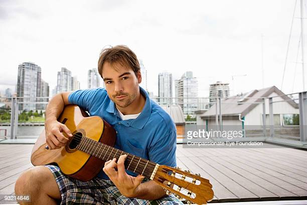 """man playing guitar with city line in background - """"compassionate eye"""" imagens e fotografias de stock"""