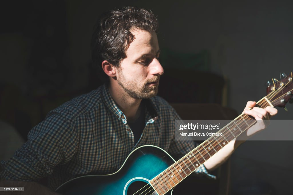 Man playing her acoustic guitar : Stock Photo
