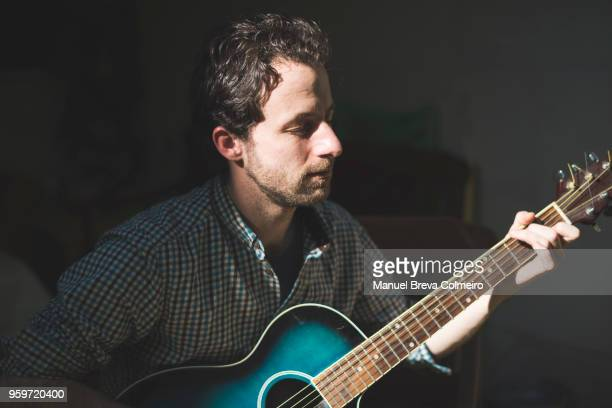 man playing her acoustic guitar - classical guitar stock photos and pictures