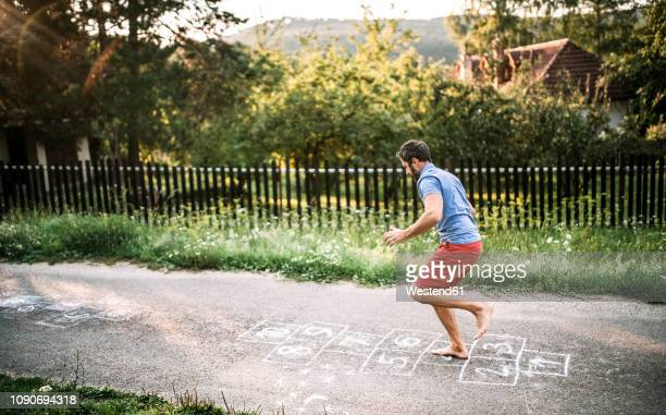 man playing hopscotch with naked feet - hopscotch stock pictures, royalty-free photos & images
