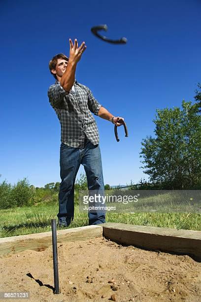 man playing horseshoes - horseshoe stock pictures, royalty-free photos & images