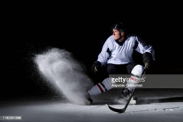 man playing ice hockey against black background - アイスホッケースティック ストックフォトと画像