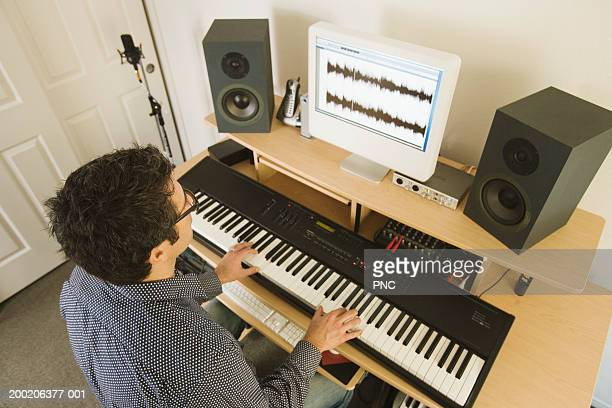 man playing keyboard through computer, elevated view - keyboard player stock photos and pictures