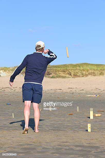 man playing kubb on the beach - man bending over from behind stock photos and pictures