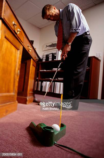 man playing mini golf in office, low angle view - putting stock pictures, royalty-free photos & images