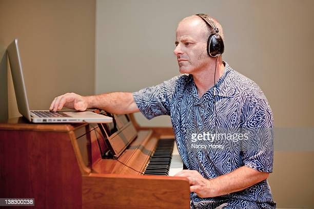 Man playing music with piano and laptop