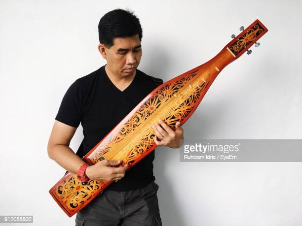 man playing musical instrument against wall - sarawak state stock pictures, royalty-free photos & images