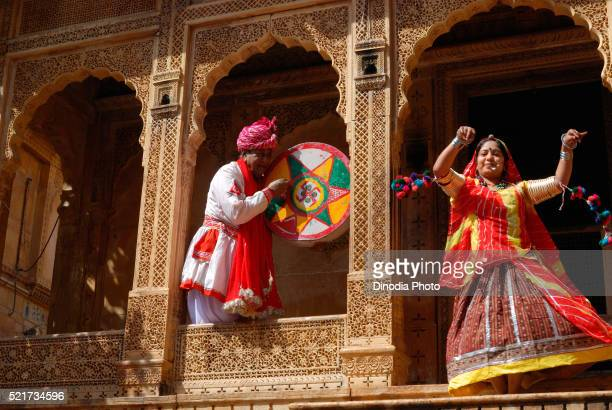 Man playing musical instrument and woman dancing, Jaisalmer, Rajasthan, India, Asia