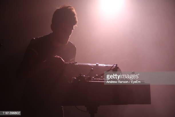 man playing musical instrument at music concert - music box stock pictures, royalty-free photos & images
