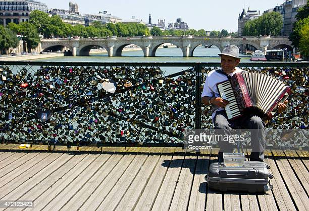 man playing near the love padlocks - french culture stock photos and pictures