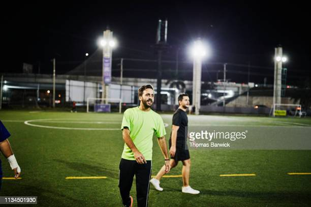 man playing nighttime soccer match with friends - mid adult men fotografías e imágenes de stock