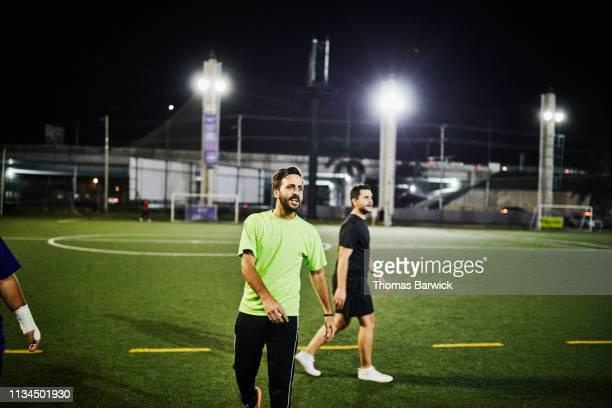man playing nighttime soccer match with friends - homens de idade mediana imagens e fotografias de stock