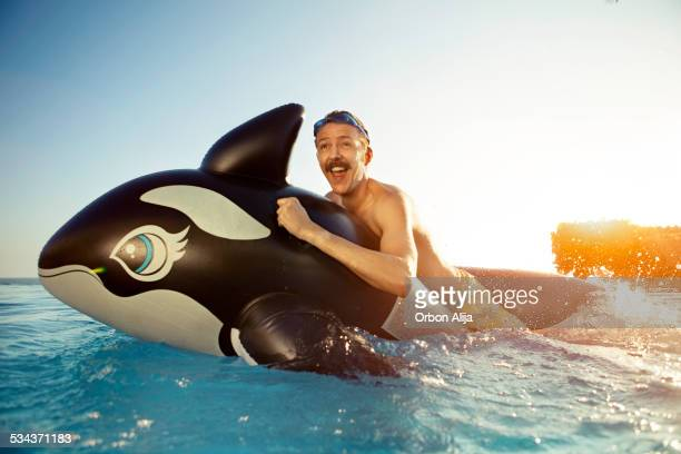 man playing on a inflated whale - drijven stockfoto's en -beelden