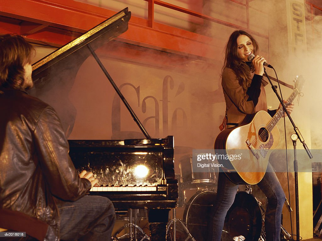 Man Playing Piano and a Woman Holding an Acoustic Guitar and Singing, on a Smokey Stage : Stock Photo