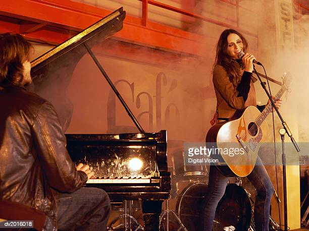man playing piano and a woman holding an acoustic guitar and singing, on a smokey stage - acoustic guitar stock pictures, royalty-free photos & images