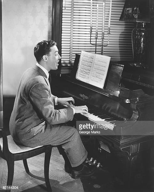 Man playing piano and singing in living room, (B&W)