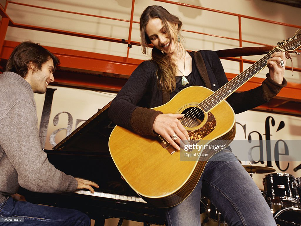 Man Playing Piano and Woman Playing Guitar Together on Stage : Stock Photo