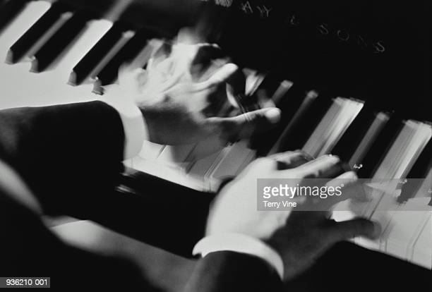 Man playing piano keyboard, close-up (blurred motion, B&W)