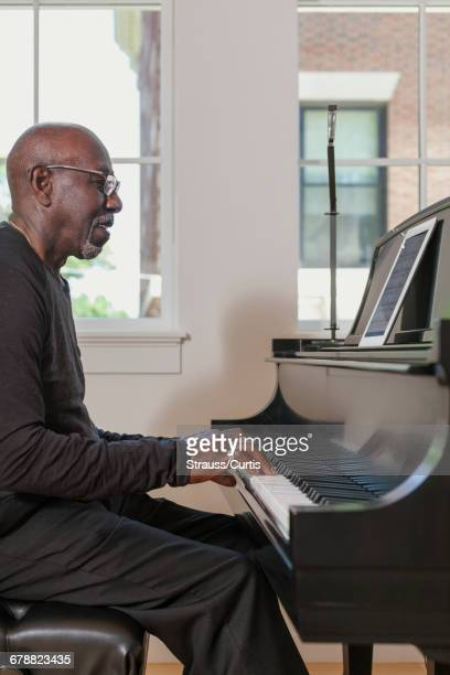 Man playing piano near window