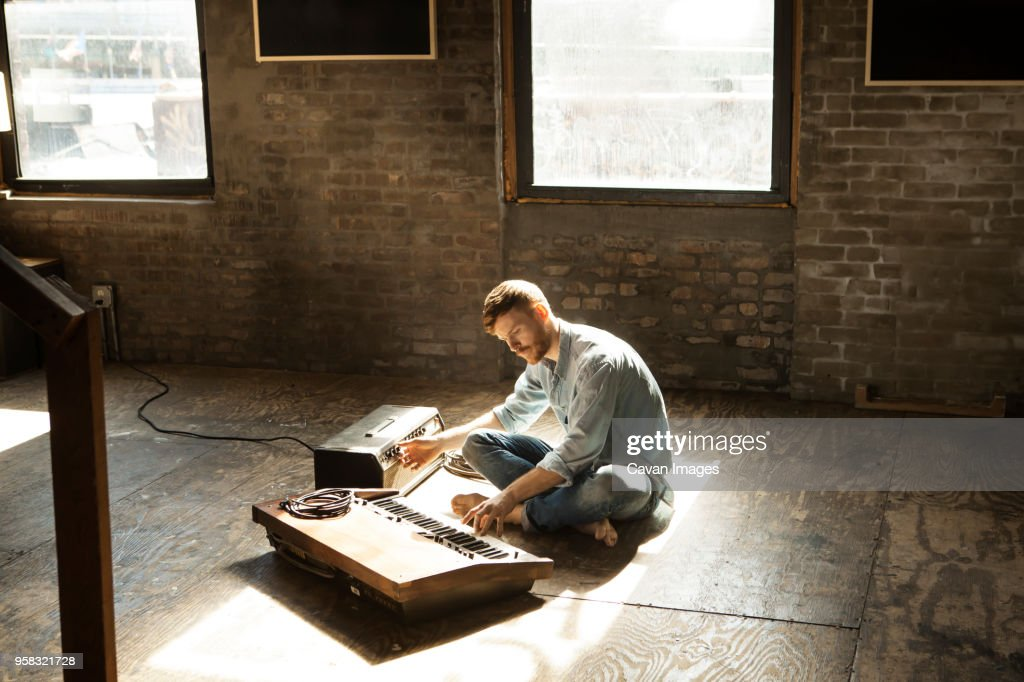Man playing piano while tuning audio equipment at home : Stock Photo
