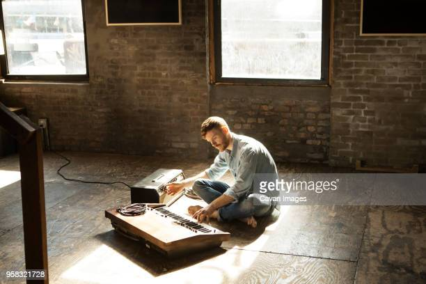 man playing piano while tuning audio equipment at home - pianist front stock pictures, royalty-free photos & images