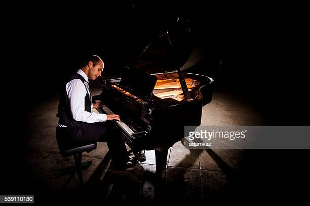 man playing piano with dramatic lighting - grand piano stock photos and pictures