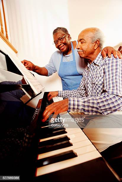 Man Playing Piano with Wife at His Side