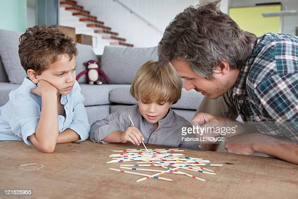 Man playing pick up sticks with his sons
