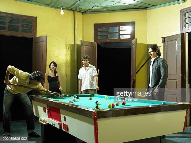 Man playing pocket billiards, friends watching