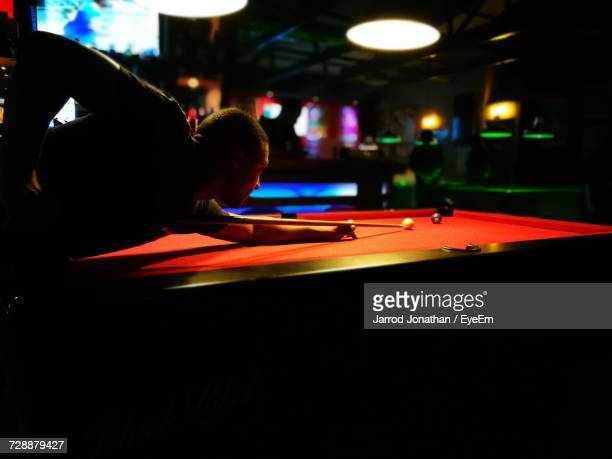 Man Playing Pool At Club
