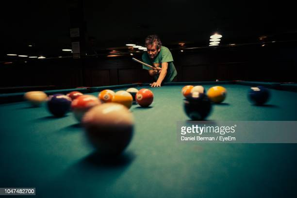 man playing pool at night - old men playing pool stock pictures, royalty-free photos & images