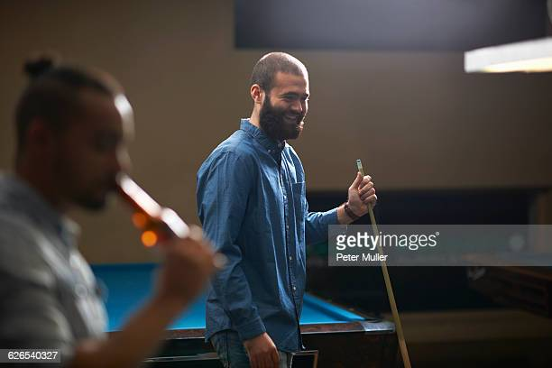 Man playing pool, friend drinking beer in foreground