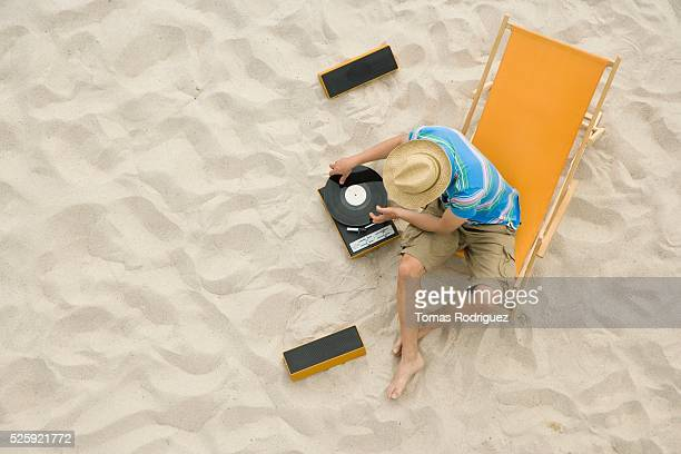 Man Playing Record Albums on a Beach