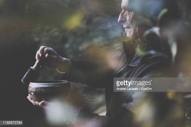 man playing rin gong while standing in forest - gong stock photos and pictures