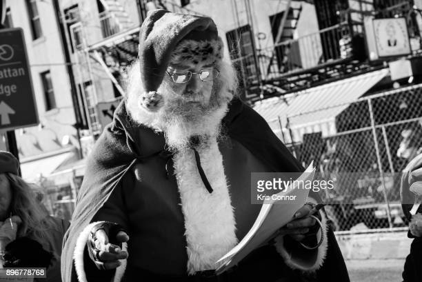Image converted to black and white A man playing Santa Clause and members of Earth is Our Mother sing Christmas carols at Petronsino Square as part...